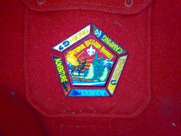 National Outdoor Badges. The location/order of the segments around the central patch does not matter. The emblem is shown centered on the right pocket of the red jac-shirt (personal comment: the emblem looks the best on the jac-shirt)